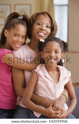 Mother and daughters smiling for the camera - stock photo