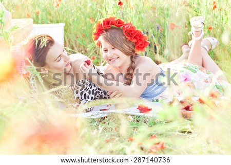 Mother and dauhter lying on the white blanket and eating strawberry in the poppy field. Summer mood - stock photo