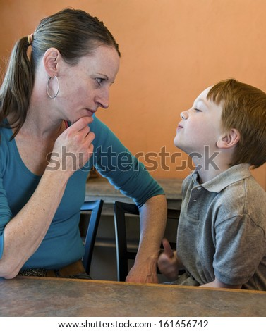 Mother and defiant young son having a standoff - stock photo