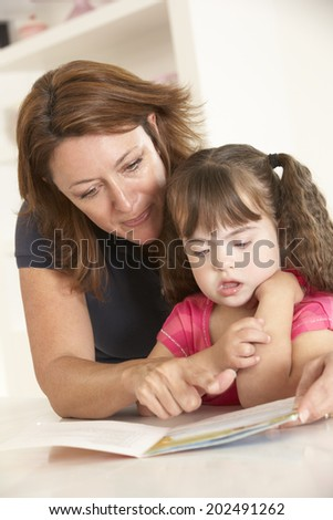 Mother and Downs Syndrome girl reading - stock photo