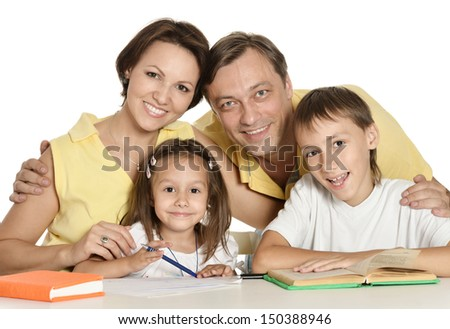 Mother and father diong homework with their children - stock photo