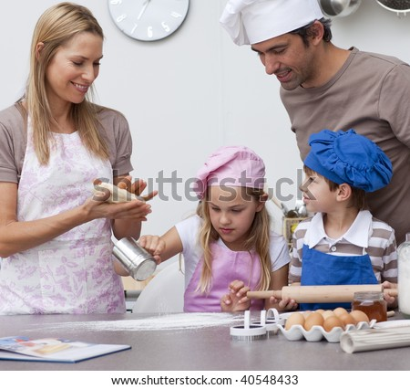 Mother and father helping children baking cookies in the kitchen - stock photo