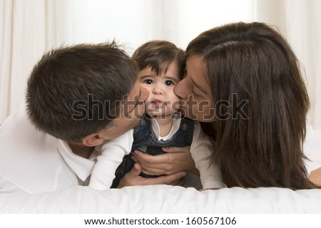 Mother and Father Kissing their Baby Girl - stock photo