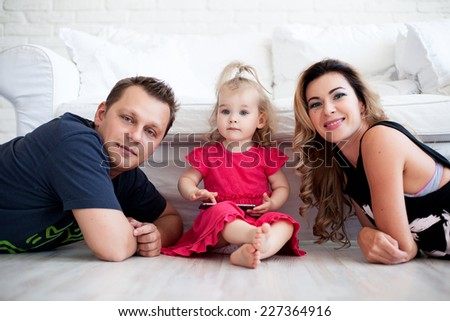 Mother and father posing while their daughter playing with phone - stock photo
