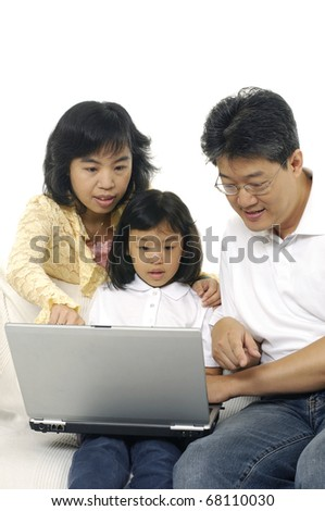 Mother and Father using a laptop with their daughter