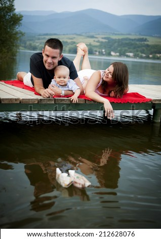 Mother and father with baby boy sitting on pier and playing with paper boat - stock photo