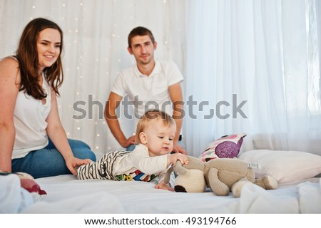 Mother and father with baby boy sitting on white bed with garland