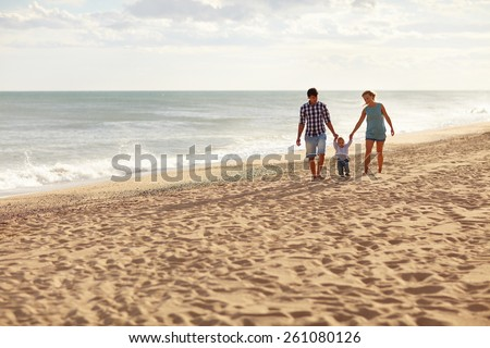 Mother and father with their toddler son walking together on a quiet beach - stock photo