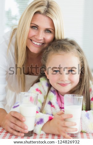 Mother and girl drinking milk while smiling in kitchen - stock photo