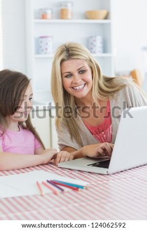 Mother and girl sitting at the kitchen smiling with laptop