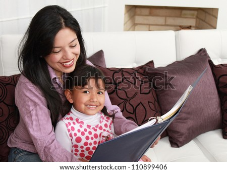 Mother and girl smiling in the home - stock photo