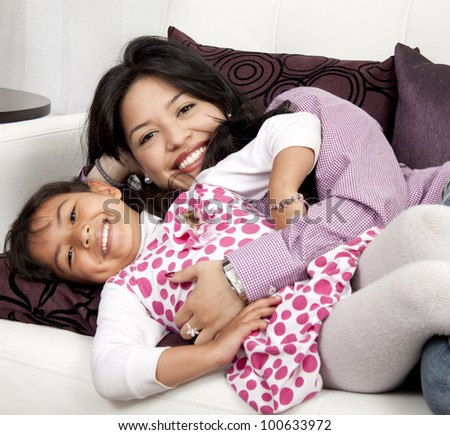 Mother and girl smiling in the living room white - stock photo
