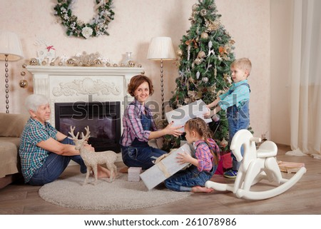 Mother and grandmother give children Christmas gifts - stock photo