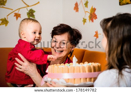 Mother and grandmother with small baby celebrating first birthday - stock photo