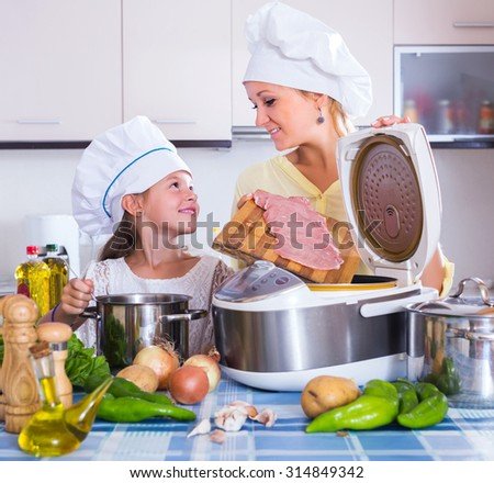 Mother and happy child preparing meat in slow-cooker - stock photo