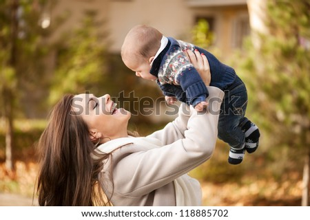 mother and her baby boy, enjoying the autumn day in the park - stock photo