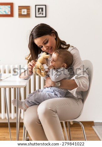 Mother and her baby boy playing with bunny toys. - stock photo