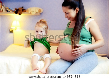 mother and her baby daughter waiting for newborn and showing tummies (focus on baby girl) - stock photo