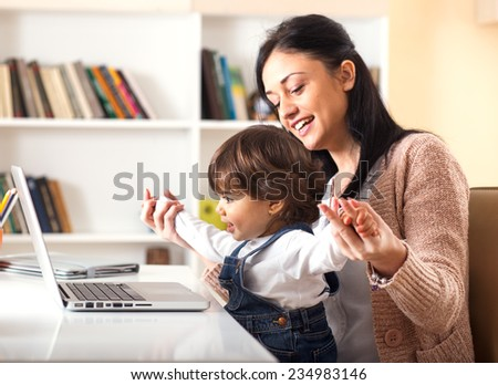Mother and her baby girl listening to music on laptop.They sitting in living room.Natural light ambient. - stock photo