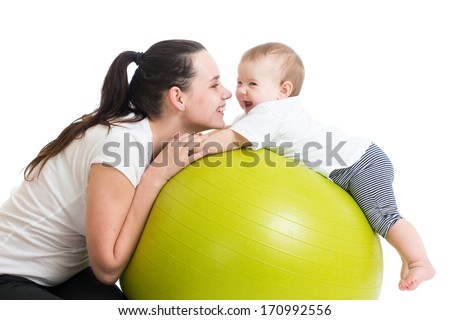 mother and her baby having fun with gymnastic ball - stock photo
