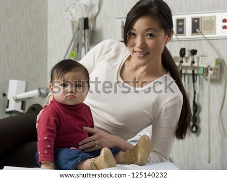 Mother and her baby in examining room - stock photo