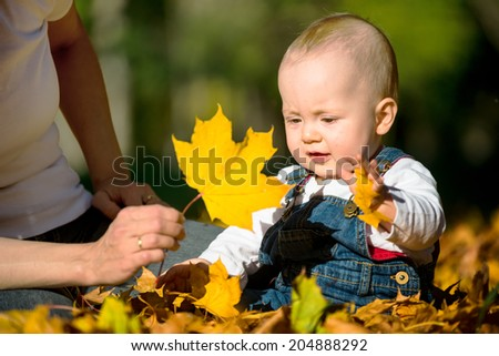 Mother and her baby playing with fallen leaves - outdoor autumn setting - stock photo