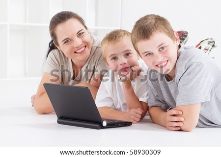 mother and her boys using laptop computer on floor - stock photo