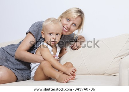 mother and her child are sitting together on the sofa.
