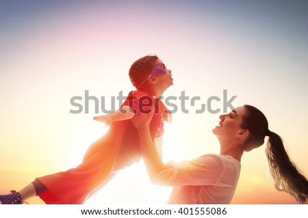 Mother and her child girl playing together. Girl in an Superhero's costume.
