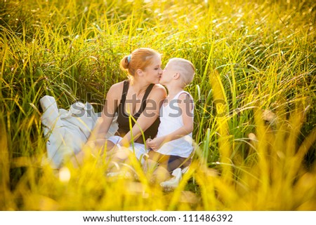 Mother and her child having fun in a park during beautiful summer evening