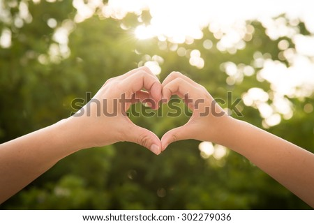 Mother and her child holding hands in heart shape framing on nature background - stock photo