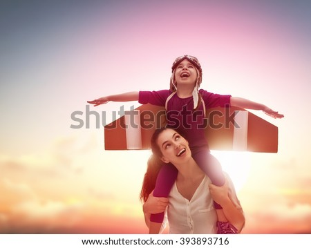 Mother and her child playing together. Little child girl plays astronaut. Child in an astronaut costume plays and dreams of becoming a spaceman. Happy loving family having fun. - stock photo
