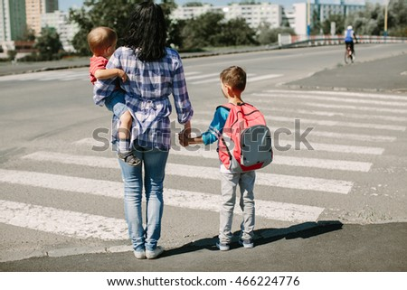 Mother and her children about to cross road on way to school