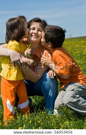 Mother and her children having fun outdoor at sunny summer day