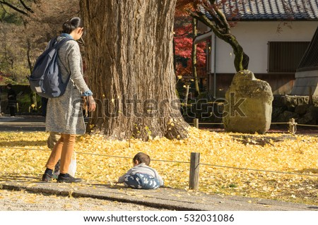 Mother and her children play with yellow leaves