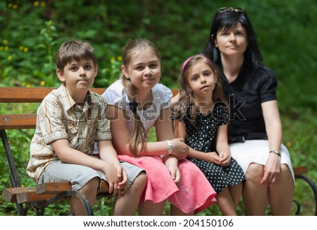 Mother and her children sitting on bench in the park at summer day - stock photo