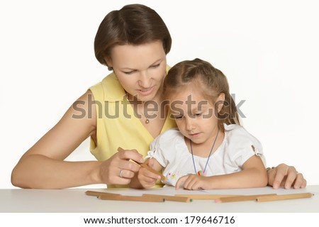 Mother and her cute daughter drawing at table