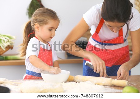 Mother and her cute daughter prepares the dough at wooden table. Homemade pastry for bread or pizza. Bakery background