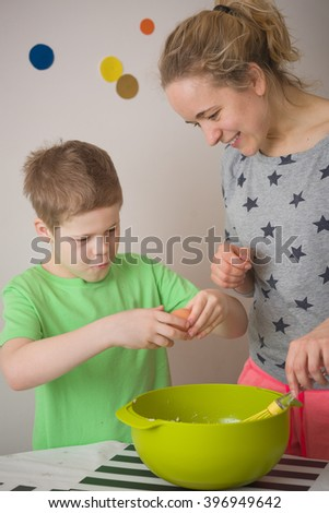 Mother and her cute kid boy baking muffins and having fun. Child and young blond mother cooking. Children and parent cooking in the kitchen. Little boy excited about his culinary experience - stock photo