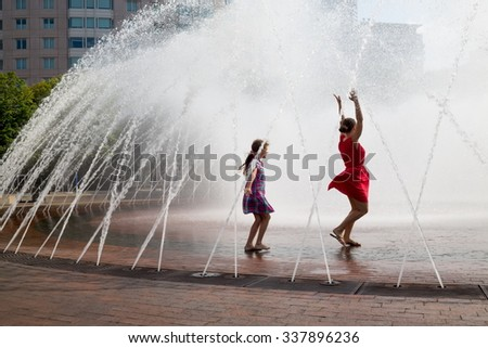 Mother and her daughter are dancing into the fountain. - stock photo