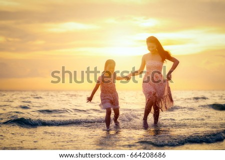 Mother and her daughter are walking happily at the beach at sunset in holiday.