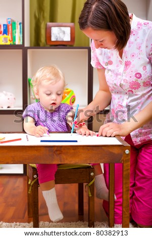 mother and her daughter drawing in the child room - stock photo
