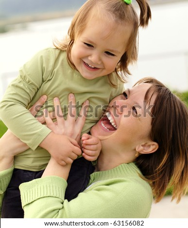 Mother and her daughter having fun outdoor - stock photo