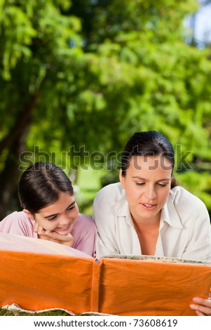 Mother and her daughter looking at their album photo - stock photo