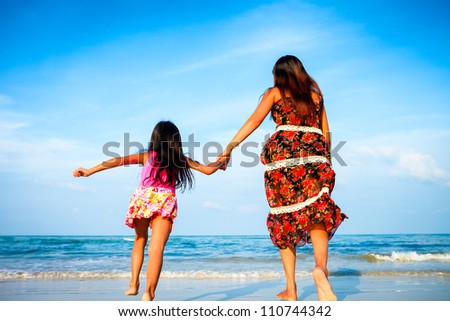 Mother and her daughter running together while holding hands on beach - stock photo