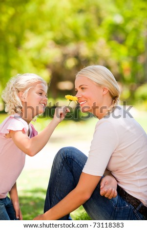 Mother and her daughter smelling a flower - stock photo