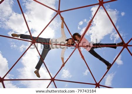 Mother and her daughter up high on the piece of playground equipment. - stock photo