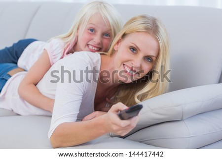Mother and her daughter watching TV in the living room - stock photo