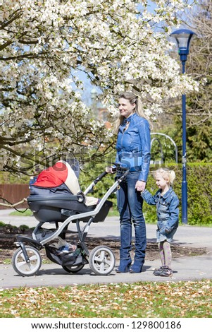 mother and her daughter with a pram on spring walk - stock photo