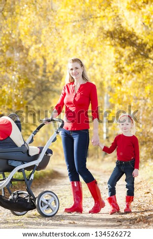 mother and her daughter with a pram on walk in autumnal alley - stock photo